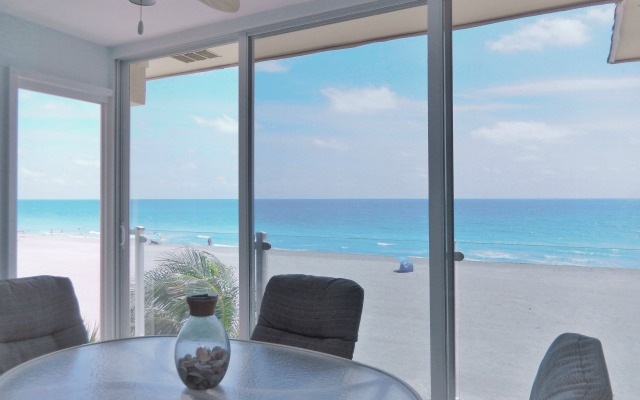Beachfront Siesta Key Lanai with floor-to-ceiling sliding glass panels and tempered glass railing