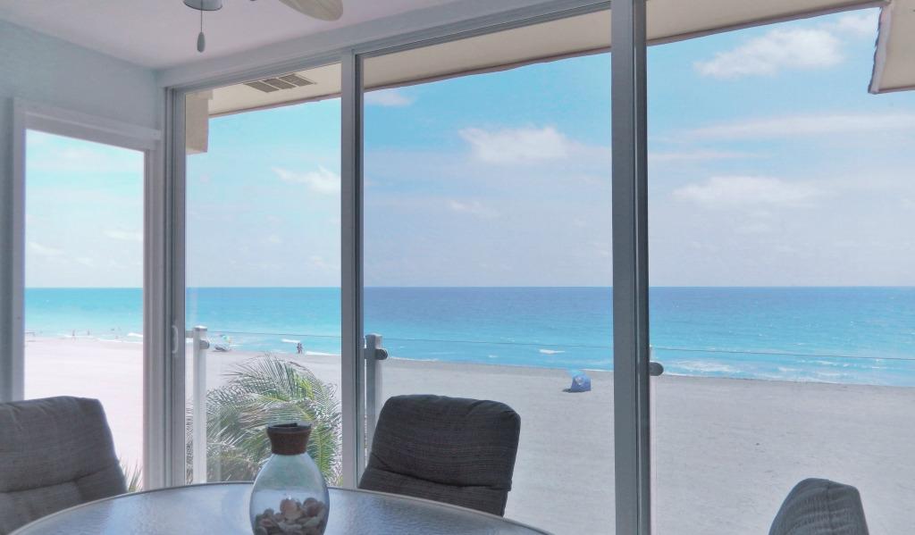 Spacious Siesta Key beachfront lanai with floor to ceiling sliding glass panels