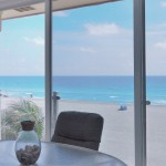 Siesta Key beachfront Lanai with floor to ceiling sliding glass panels and tempered glass railing for unobstructed view