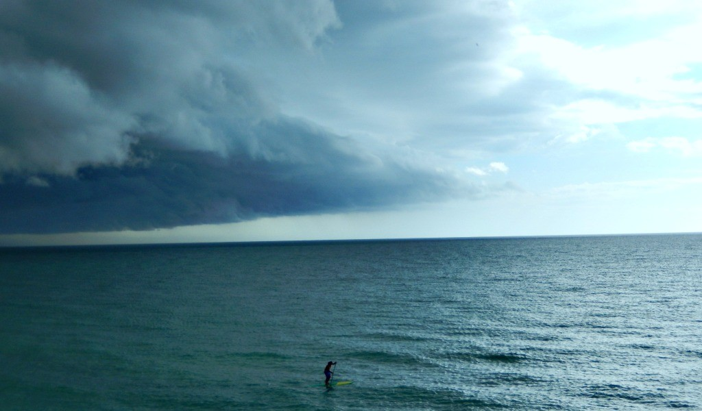 Paddleboarder trying to stay ahead of incoming storm
