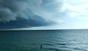 Paddleboarder running from the incoming storm
